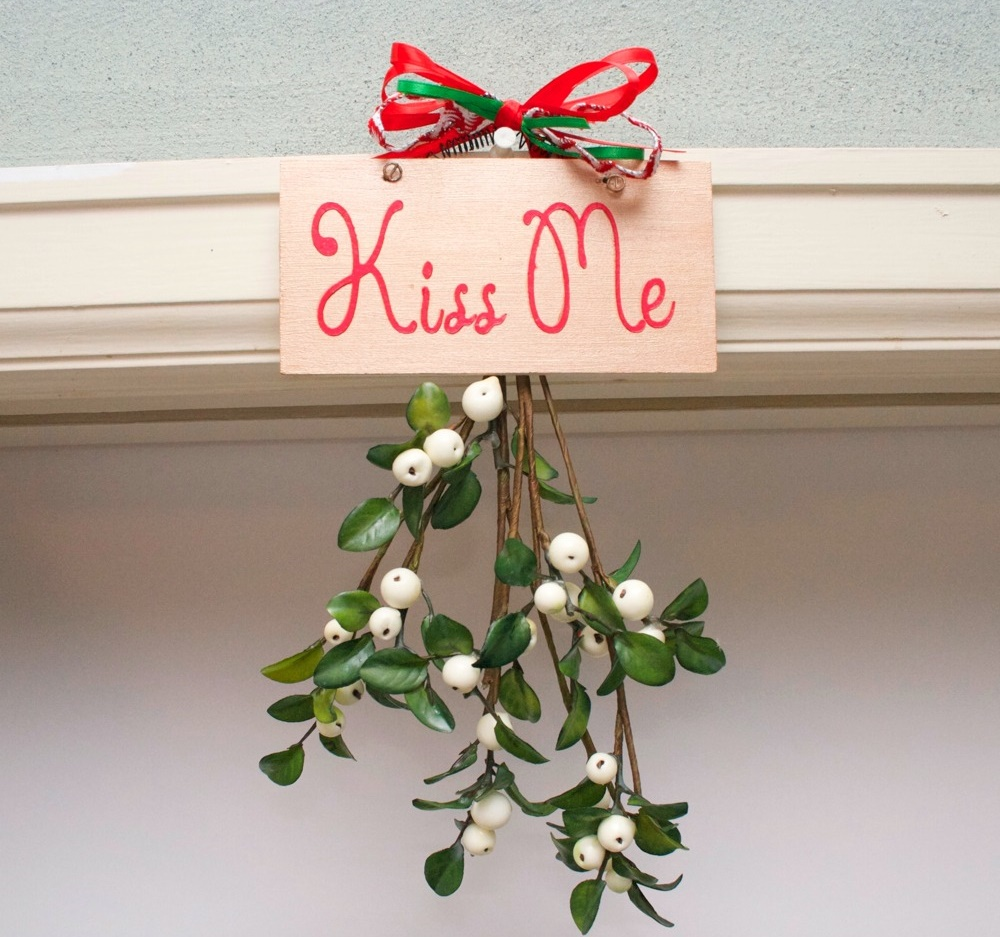 "Mistletoe hanging in a doorway with a sign that says, ""kiss me."""