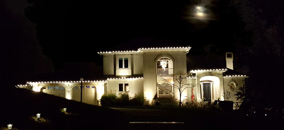 House at night with lights along roofline