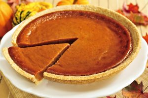 Whole pumpkin pie with a slice cut out